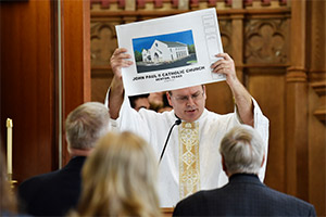 Father Kyle Walterscheid shows the blueprints of St. John Paul II Church as he thanks all those who help to build the church during a special Dedication Mass in Denton, Feb. 15, 2020. (NTC/Ben Torres)